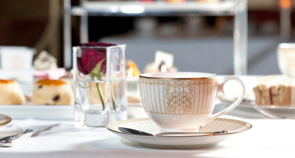Si hablamos de té en términos de tradición y protocolos, inmediatamente nos vienen a la mente nuestros vecinos británicos y nos lo imaginamos tazas de té inglés en mano, meñique levantado compartiendo cotilleos mientras revuelven con sumo cuidado su earl grey. Eso nos viene a la mente, claro. Y aunque lo cierto es que el té tiene su origen real en Japón y no en Inglaterra, la tradición del 'afternoon tea' británico llega a nuestros días tan viva que se hace muy protagonista en cuanto a imágenes mentales costumbristas. Y de tan lejos que viene, del siglo XVII y de las vivencias en la corte británica. Esa misma corte en la que la hora de las tazas de té inglés aún se mantiene. En nuestras tierras, esta costumbre, pese a no ser desconocida, lo cierto es que no está tan arraigada, aunque son muchos los que disfrutan celebrando sus afternoon tea acompañados de amigos, o los bares, restaurantes y hoteles que ofrecen la experiencia en sus cartas. Por eso, es importante echar un ojo al catálogo de tazas de te inglés personalizadas en la medida en que son una tendencia en cuanto a artículos publicitarios y regalos de empresa. Pero descubramos primero un poco más de esta tradición británica, a la que no le falta historia, normas y por supuesto, curiosidades. Tea time! La tradición del uso de tazas de te inglés nace en el siglo XVII de la mano de la duquesa de Bedford, la princesa Catalina de Braganza, originaria de Portugal quien, casada con el rey Carlos II, fue quien instauró la costumbre. Y de la manera más casual, en realidad. Por lo visto, la duquesa era propensa a sufrir desfallecimientos, y por esa razón pedía a sus sirvientes que le preparase pequeñas merendolas con té y pastas de forma previa a la cena. Le empezó a coger gusto a la costumbre hasta el punto de empezar a invitar a sus amigos a esas merendabas, sentando las bases de lo que llega a nuestros días popularizado como el Afternoon Tea. Una tradición que se mantiene en los círculos de alto nivel y en el entorn